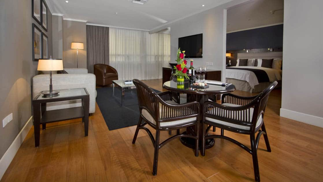 The leading suite at the Hotel Oro Verde in Guayaquil, Ecuador offers modern furniture, a seating area with a table, chairs, and a couch, and a large bed