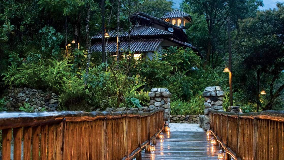 A wooden bridge and railing lead to a stone pathway that winds through 12 acres of lush vegetation with rich biodiversity at the Inkaterra Machu Picchu Pueblo Hotel, a National Geographic Unique Lodge of the World.