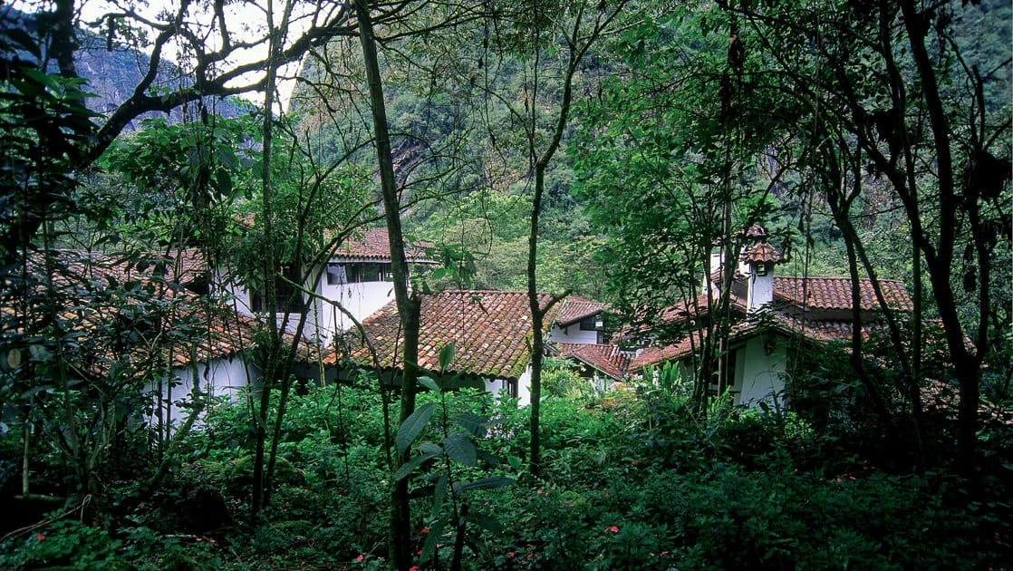 Adobe casitas with red tiled roofs are nestled in the cloud forest at the Inkaterra Machu Picchu Pueblo Hotel, a National Geographic Unique Lodge of the World.