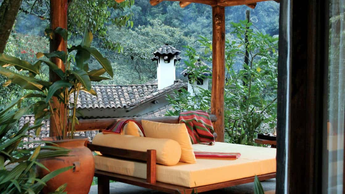 A terrace with a sitting area and loveseat overlooks a lush garden at the Inkaterra Machu Picchu Pueblo Hotel, a National Geographic Unique Lodge of the World.