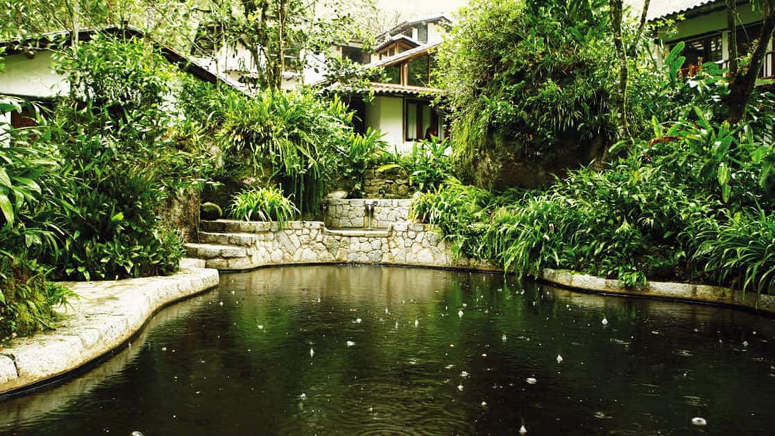A pond surrounded by stone pathways, lush gardens, and adobe casitas at the Inkaterra Machu Picchu Pueblo Hotel, a National Geographic Unique Lodge of the World.