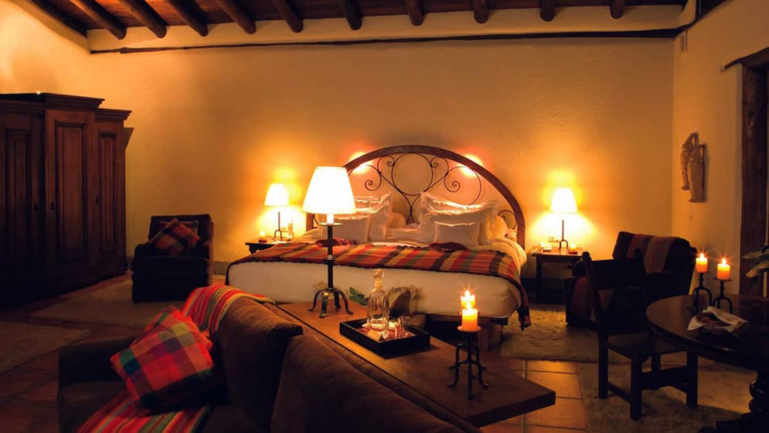 One of the rooms at the Inkaterra Machu Picchu Pueblo Hotel, with a king-sized bed, couch, and reading lights, designed with Andean style and the exquisite handicraft of local artisans and tasteful furnishings.