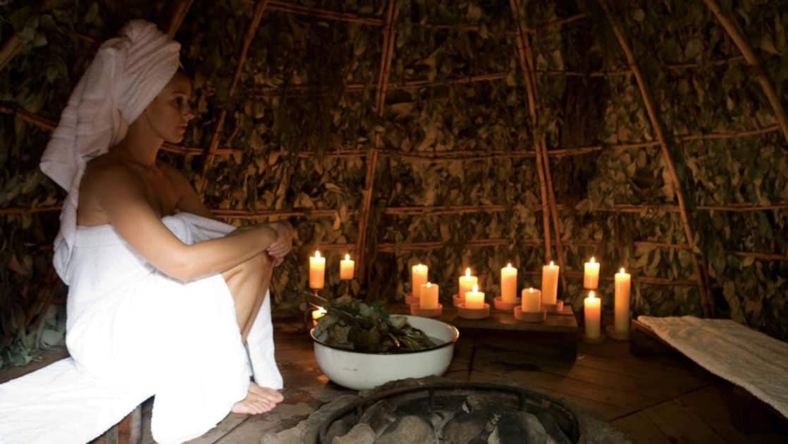 A person wrapped with towels around their body and hair sits in a room lit by candles while a bowl of local botanical extracts (mint, eucalyptus and orchids) provides a spiritual, sensual and soothing experience at the Inkaterra Machu Picchu Pueblo hotel.