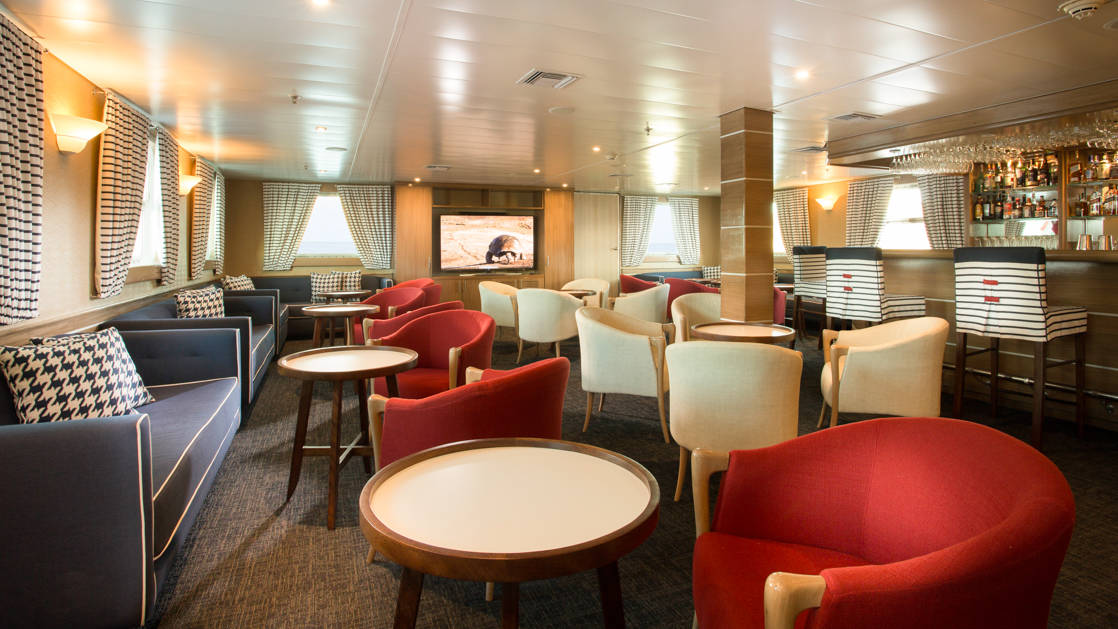 Isabella II lounge with bar, couches, chairs, tables and large viewing windows.