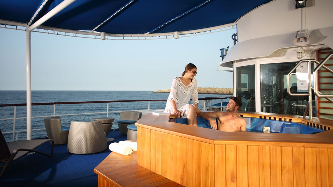Couple relaxing and soaking in the jacuzzi on the deck of the Isabella II in the Galapagos.