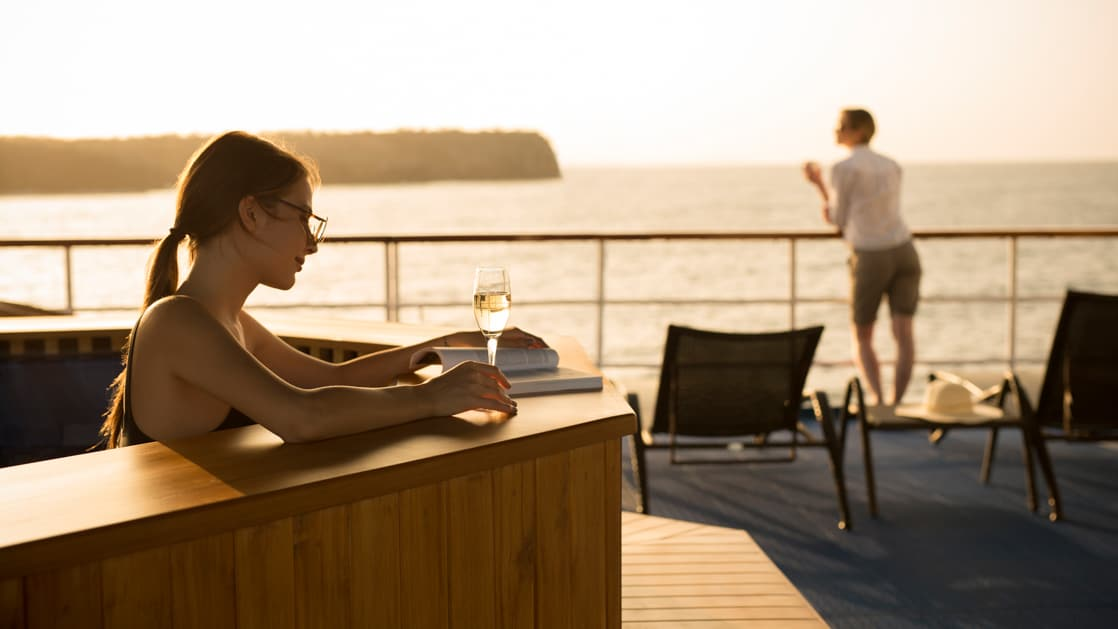 A woman enjoying a glass of wine and reading while relaxing in the jacuzzi with a male passenger leaning over the railing of the deck enjoying the view on the Isabella II.