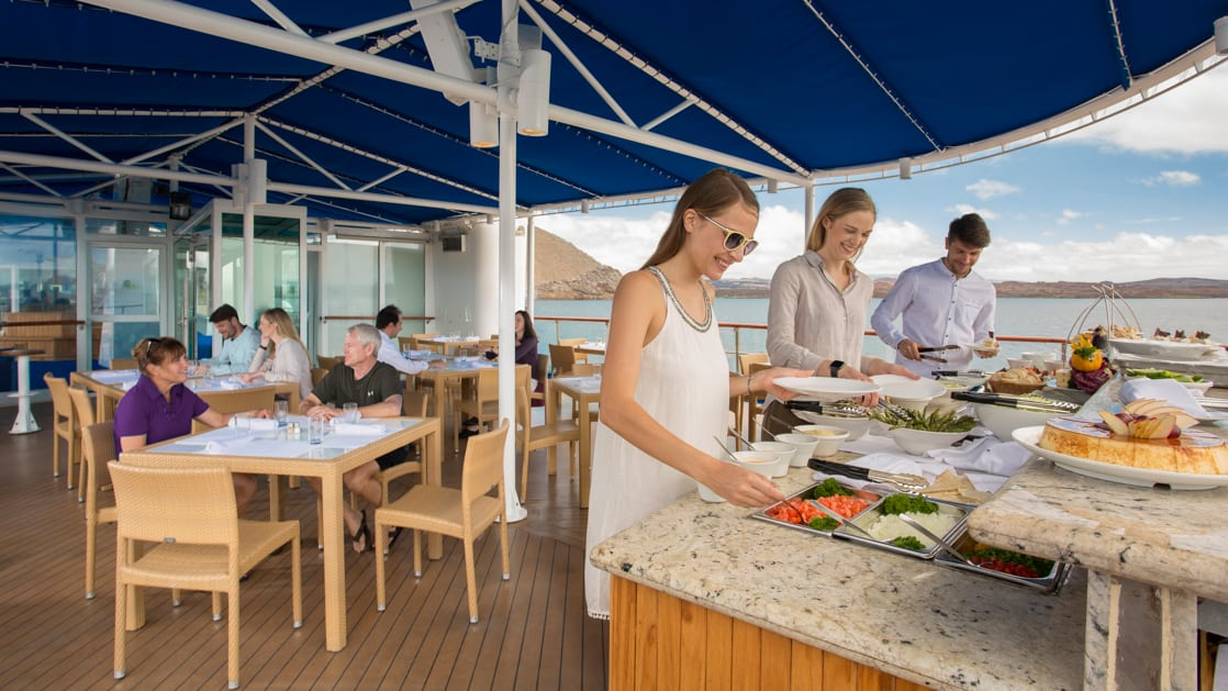 Outdoor dining on the sundeck with passengers enjoying a buffet meal aboard the Isabella II.