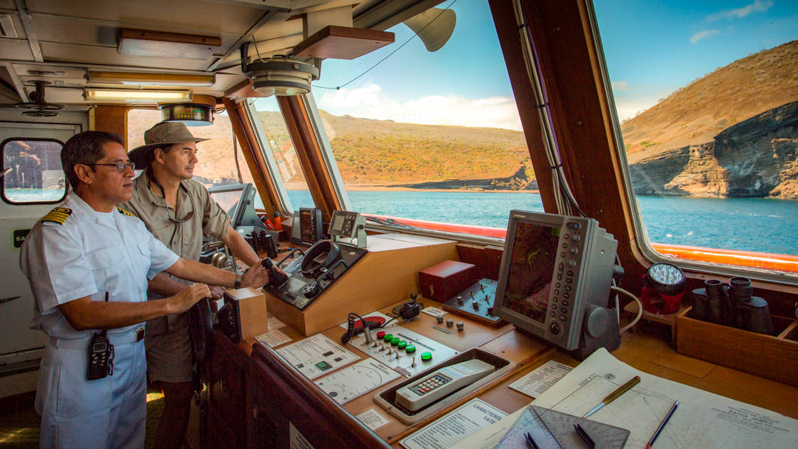 Captain and mates navigating the waters in the Galapagos from the bridge of the Isabella II.