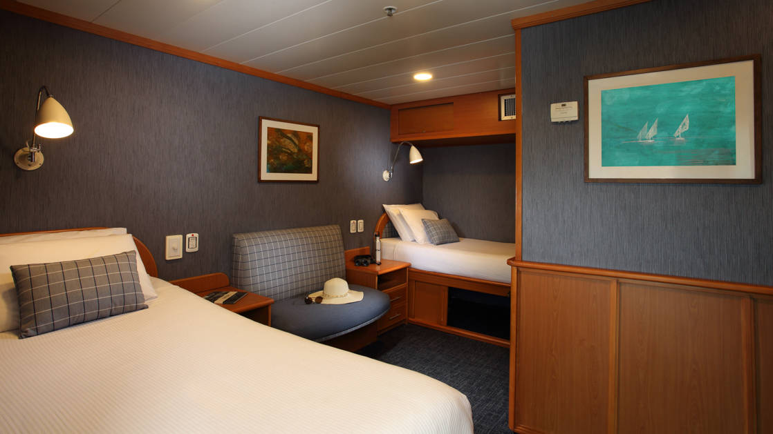 Isabela II Classic Cabin with twin beds, seating, nightstand and reading lights.