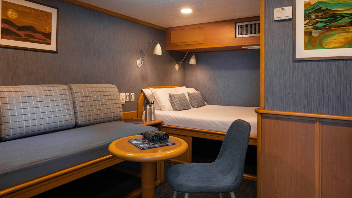 Isabela II Classic Family Cabin with double bed, fold out twin sofa, small coffee table and chair, nightstand and reading lights.