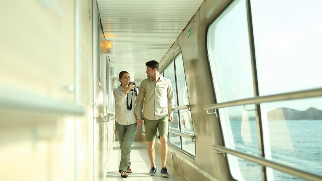Happy couple walking along the outdoor aisle way on board the Isabella II.