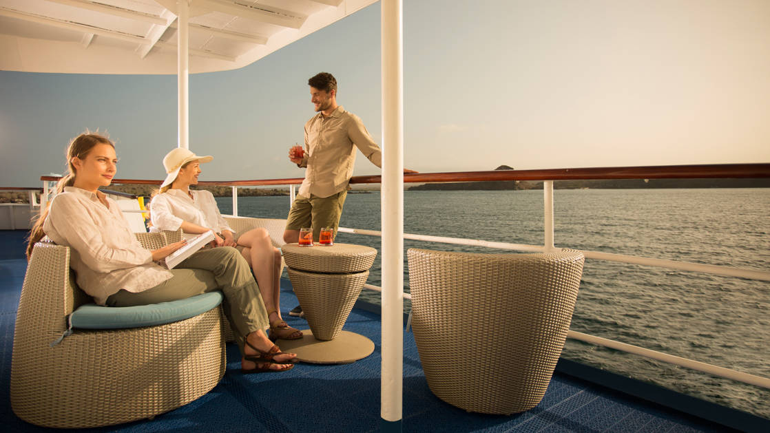 Passengers relaxing on outdoor seating on the deck of the Isabella II at sunset in the Galapagos.