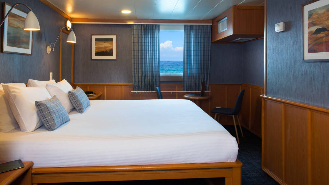 Isabela II Owners Cabin with double bed, nightstand, window, small table and chairs.