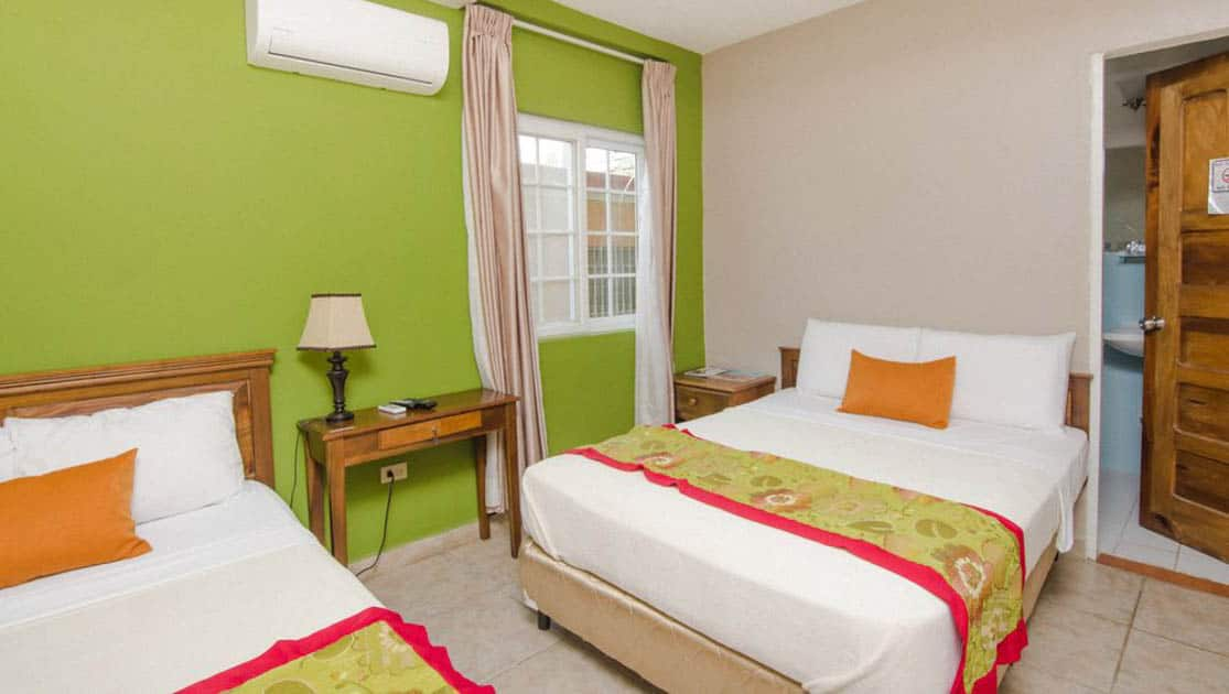 A double room with two queen-sized beds is bright and comfortable with green walls at La Casa de la Abuela, a relaxing hotel in Panama