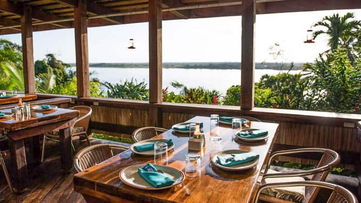 A table is set for fine dining in the open-air room overlooking the clear waters of the New River Lagoon at the Lamanai Outpost, a sustainable eco jungle lodge in Belize