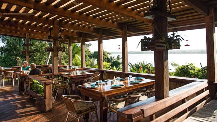 Open-air dining with tables and chairs overlooking the clear waters of the New River Lagoon at the Lamanai Outpost, a sustainable eco jungle lodge in Belize