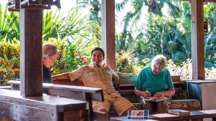 A group of people relax in the open-air lounge overlooking the New River Lagoon, near the Maya ruins, at the lamanai outpost, an eco jungle lodge in Belize