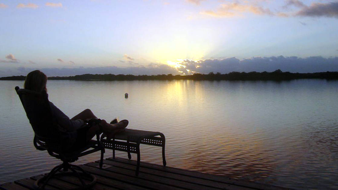 A guest sits in a lounge chair on the dock and watches the sun set over the clear water of the New River Lagoon, just in front of the Lamanai Outpost, an eco lodge in Belize