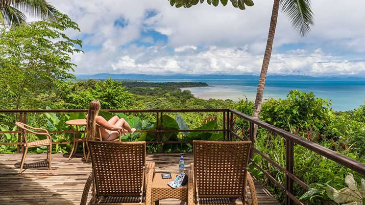 Guests sitting in lounge chairs looking out over the ocean from a balcony at the Lapa Rios Eco Lodge in Costa Rica on the sun deck