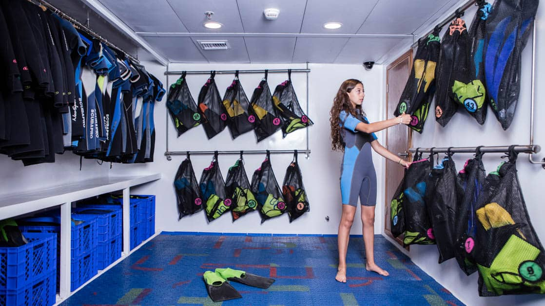 Galapagos Legend snorkeling gear room with woman standing in wetsuit picking out snorkel and mask.