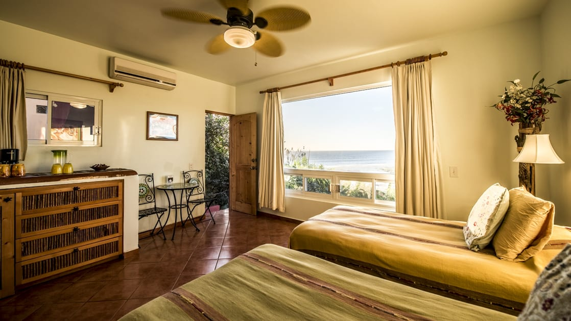 A room inside a private condo with two beds and a terrace overlooking the Pacific ocean at the boutique Baja hotel Los Colibris Casitas