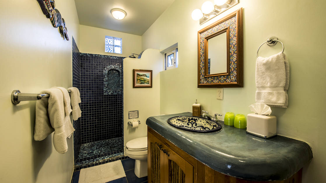 A bathroom inside a private condo with a vanity, mirror, sink, toilet, shower, and fresh towels at the boutique Baja hotel Los Colibris Casitas