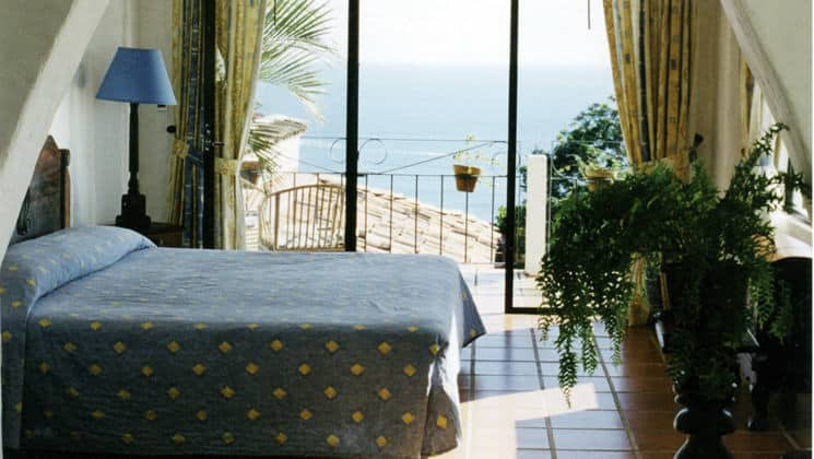A room at La Mariposa Hotel with a queen-sized bed, private balcony, tiled floor offers guests comfort and relaxation with ocean views