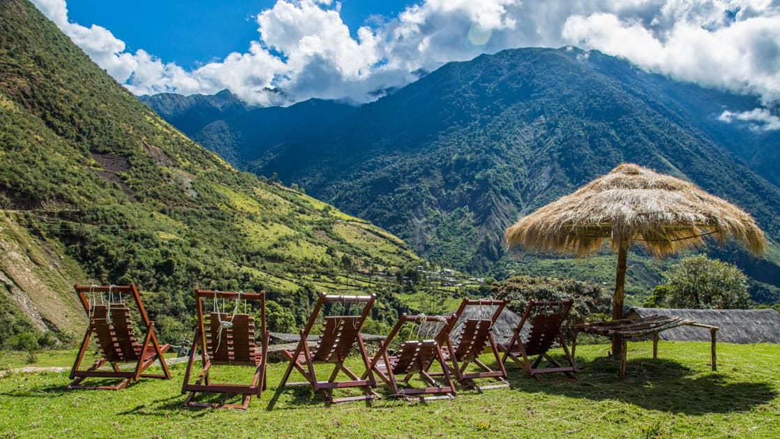 Lounge chairs and a thatch umbrella face the lush green landscape of the Andean hills, near the Colpa Lodge, part of the Mountain Lodges of Peru on the Inca Trail to Machu Picchu