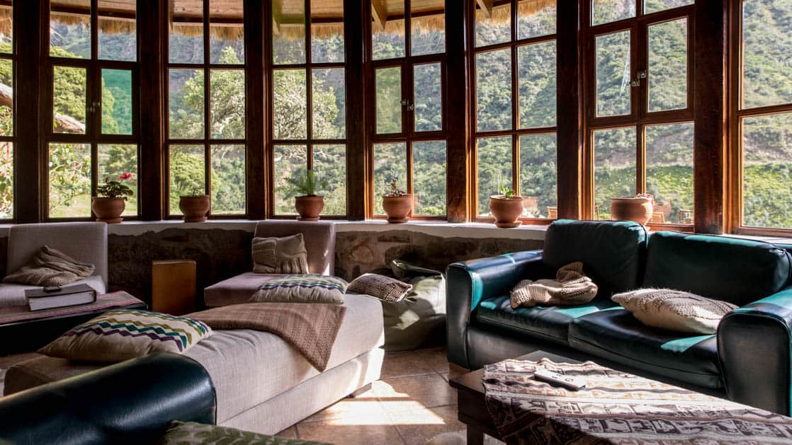 The lounge with couches, tables, potted plants, and large windows facing the forest and mountains at the Colpa Lodge, part of the Mountain Lodges of Peru on the Inca Trail to Machu Picchu