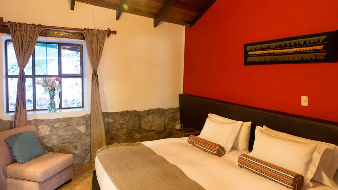 A room with a red wall and traditional Andean architecture at Lucma Lodge, a sustainable hotel built into the mountainside. It is part of the mountain lodges of Peru, along the Inca trail to Machu Picchu