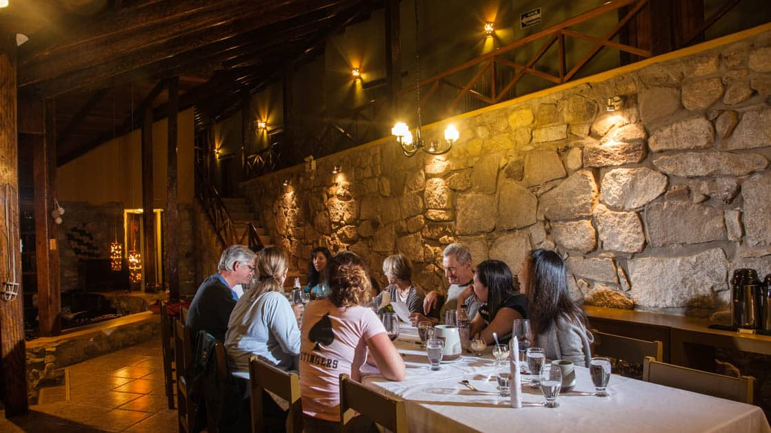 Guests sit down at a table inside the stone-walled dining room at at Lucma Lodge, a sustainable hotel built into the mountainside. It is part of the mountain lodges of Peru, along the Inca trail to Machu Picchu