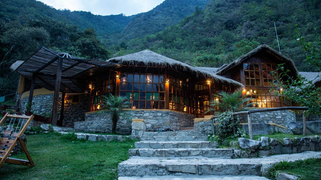 At dusk, lights glow on the exterior of Lucma Lodge in Lucmabamba, built right into the mountainside and flanked by an avocado orchard. It is part of the mountain lodges of peru, a sustainable accommodation along the inca trail to Machu Picchu