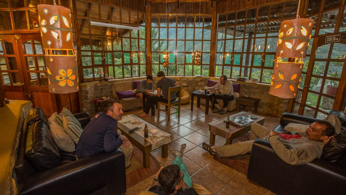 Guests relax with beers and games at the lounge inside the at Lucma Lodge, a sustainable hotel built into the mountainside. It is part of the mountain lodges of Peru, along the Inca trail to Machu Picchu