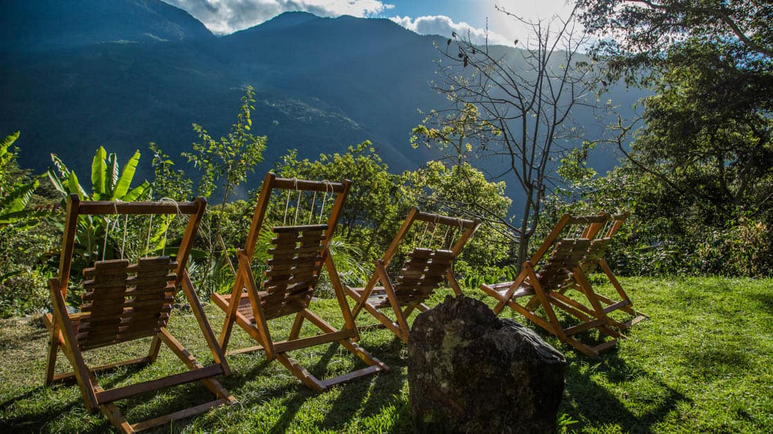 Lawn chairs face lush green vegetation and the Andean hills on a sunny day at the Lucma Lodge, one of the mountain lodges of Peru along the inca trail to Machu Picchu