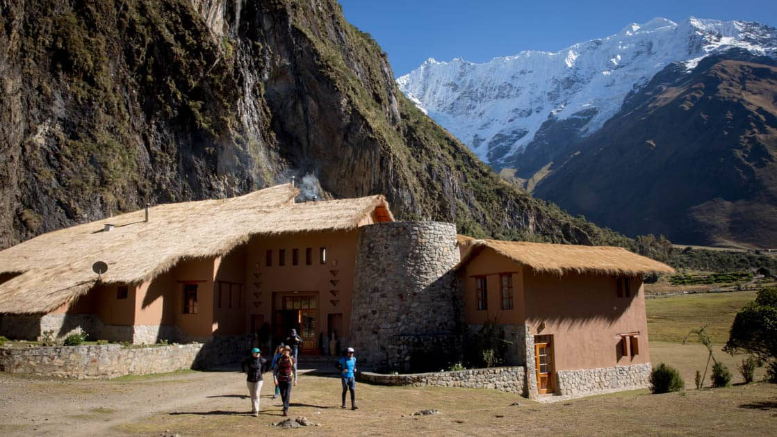 A group of trekkers stand outside the Salkantay Lodge, Adventure Resort, one of four hotels that are part of the Mountain Lodges of Peru on the Inca Trail to Machu Picchu. The building has thatch roofs and stands beneath a towering mountain in the Andes.