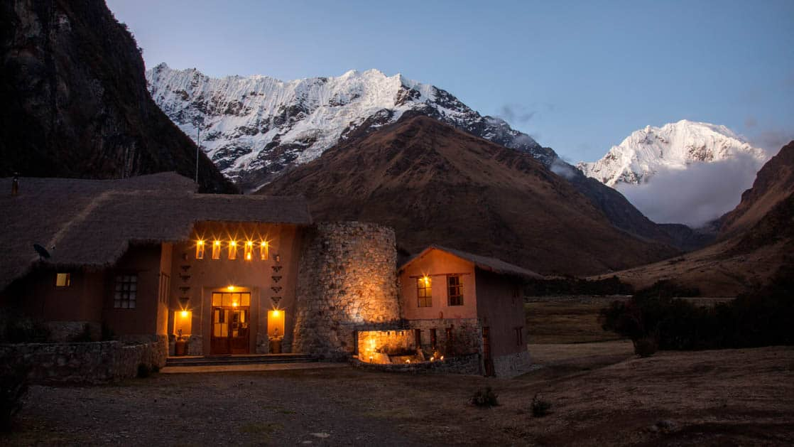 Lights glow from within the Salkantay Lodge and Adventure Resort, one of four hotels at the Mountain Lodges of Peru on the Inca Trail to Machu Picchu, as dusk settles on the snow-capped mountains in the distance