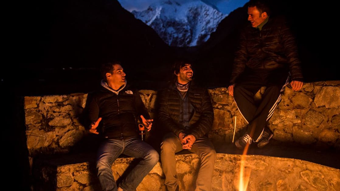 Three people sit on a stone ledge with a fire glowing in front of them, as darkness drapes the Andes in the distance, at the Salkantay Lodge and Adventure Resort, one of four hotels at the Mountain Lodges of Peru on the Inca Trail to Machu Picchu