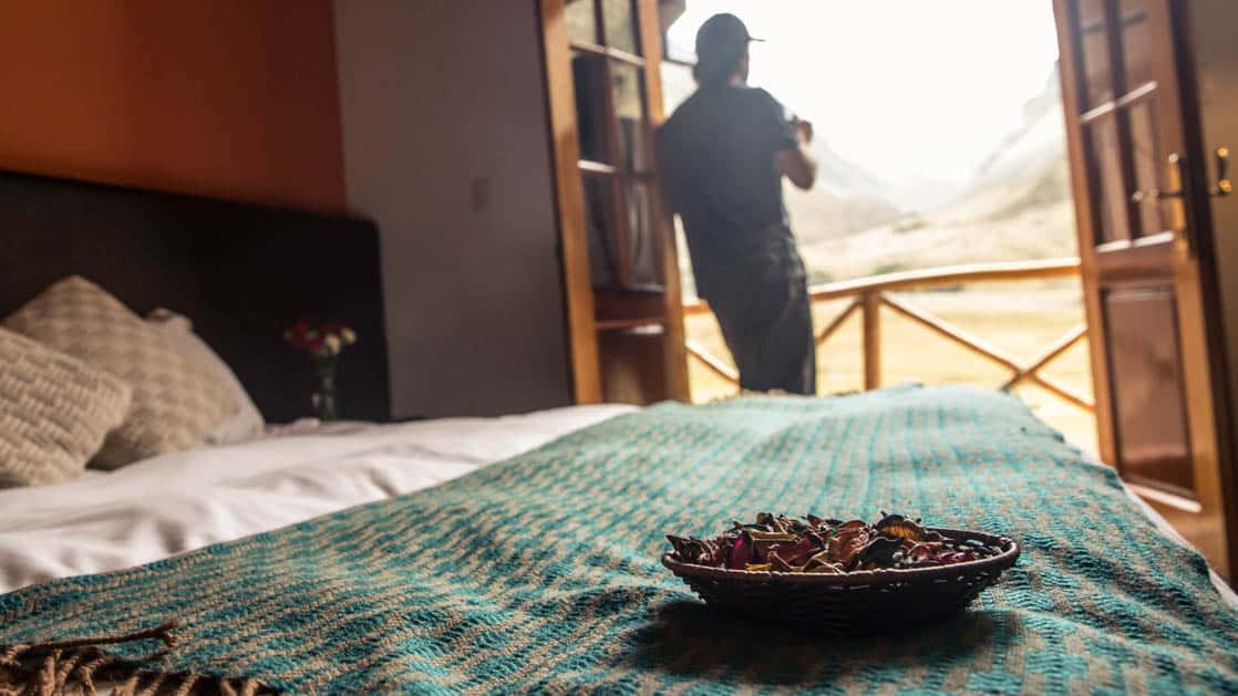 A person stands on the private balcony adjacent to a bedroom and sips a hot drink at the Salkantay Lodge and Adventure Resort, one of four hotels at the Mountain Lodges of Peru on the Inca Trail to Machu Picchu.