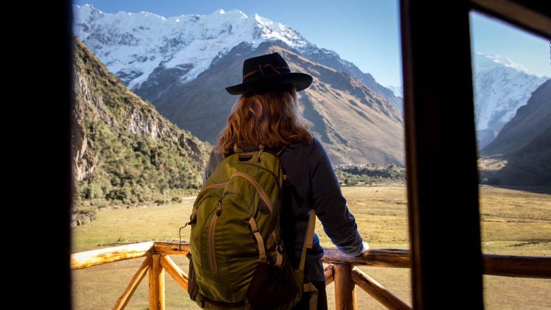 A woman stands on the porch ready to go hike into the snow-capped mountains in the distance, with a backpack, at the Salkantay Lodge and Adventure Resort, one of four hotels at the Mountain Lodges of Peru on the Inca Trail to Machu Picchu.