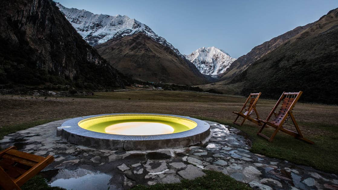 An outdoor pool is set in stone with snow-capped mountains in the distance at the Salkantay Lodge and Adventure Resort, one of four hotels at the Mountain Lodges of Peru on the Inca Trail to Machu Picchu