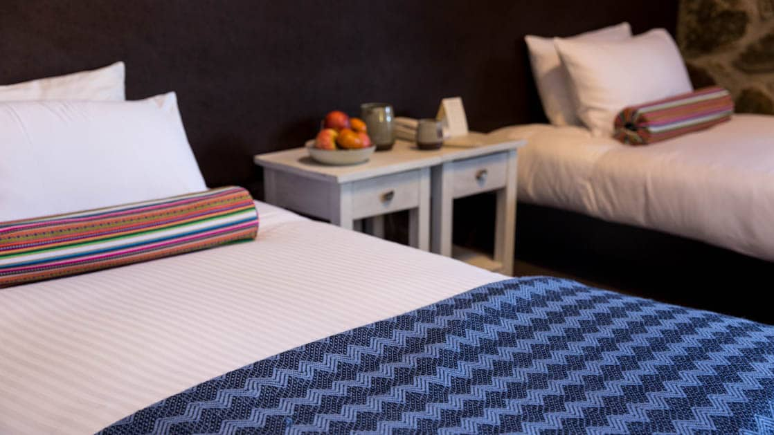 A bed is made with a traditional Andean print blue duvet and pillows, next to a nightstand at the Wayra Lodge in Peru, a sustainable hotel along the Inca Trail to Machu Picchu
