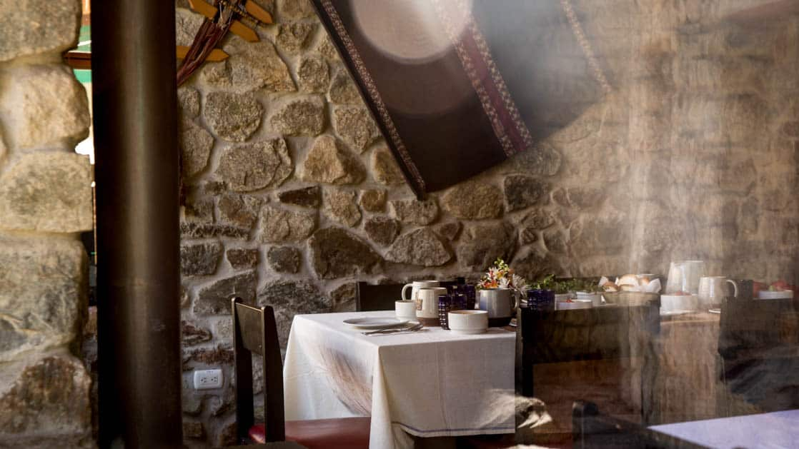 A table is set with white linens and fine dining placements inside the stone-walled dining room at the Wayra Lodge in Peru, a sustainable hotel along the Inca Trail to Machu Picchu