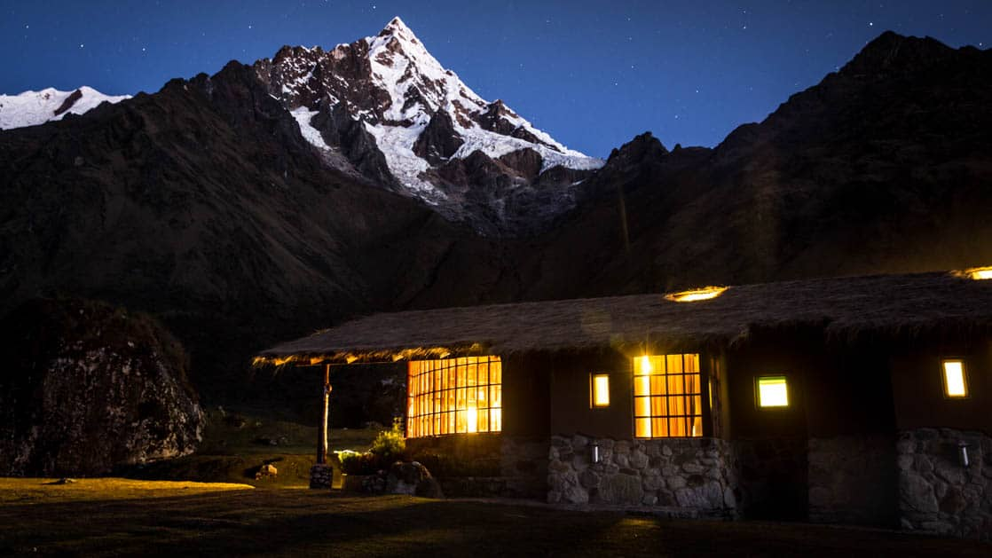 Lights inside the Wayra Lodge glow through the windows, as the building settles in for the night under snow-capped Andean peaks, along the Inca Trail to Machu Picchu in Peru
