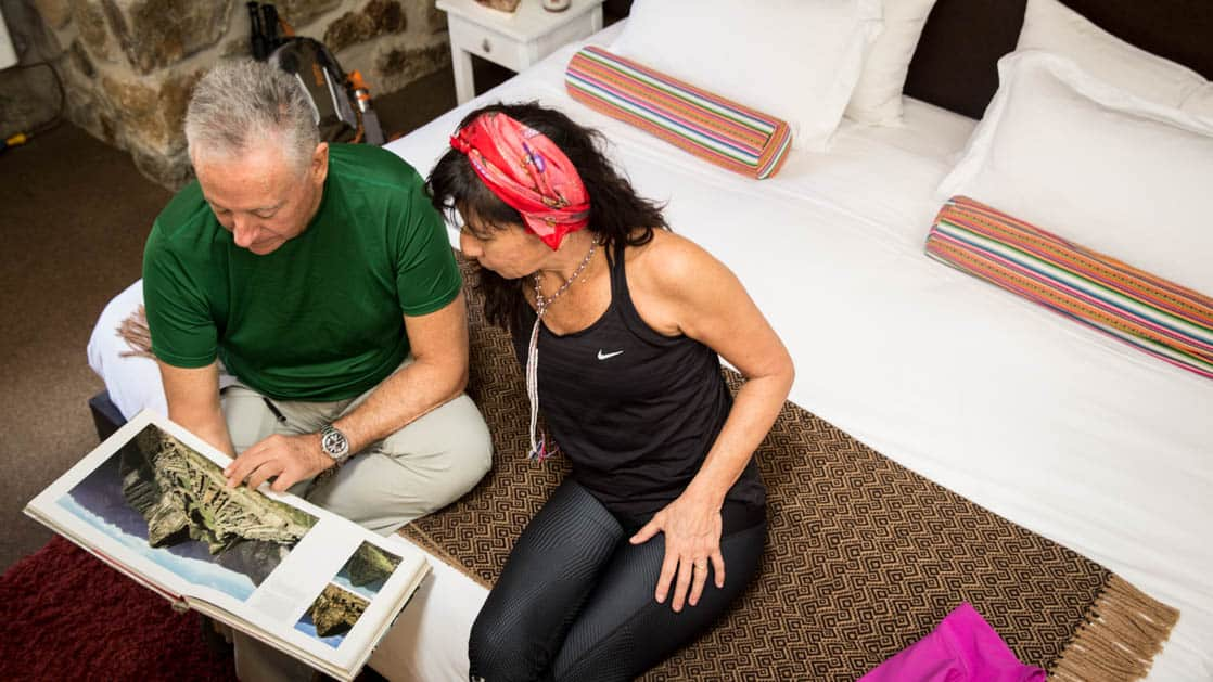Two guests admire photos of Peru in a book in their room at the Wayra Lodge, a sustainable hotel along the Inca Trail to Machu Picchu