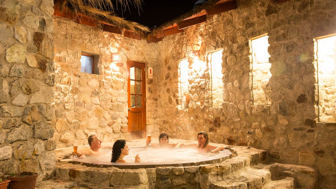 Guests relax inside the stone-walled spa with a jacuzzi at the Wayra Lodge, a sustainable hotel along the Inca Trail to Machu Picchu in Peru