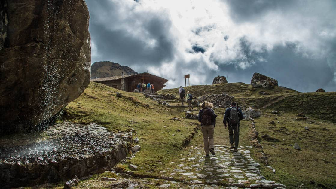 Trekkers hike up a pathway of grass and stone toward the Wayra Lodge in Peru, a sustainable hotel along the Inca Trail to Machu Picchu