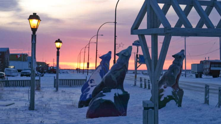 Wolf statues at sunset outside Churchill Hotels on the snow-covered streets of the Arctic town of Churchill