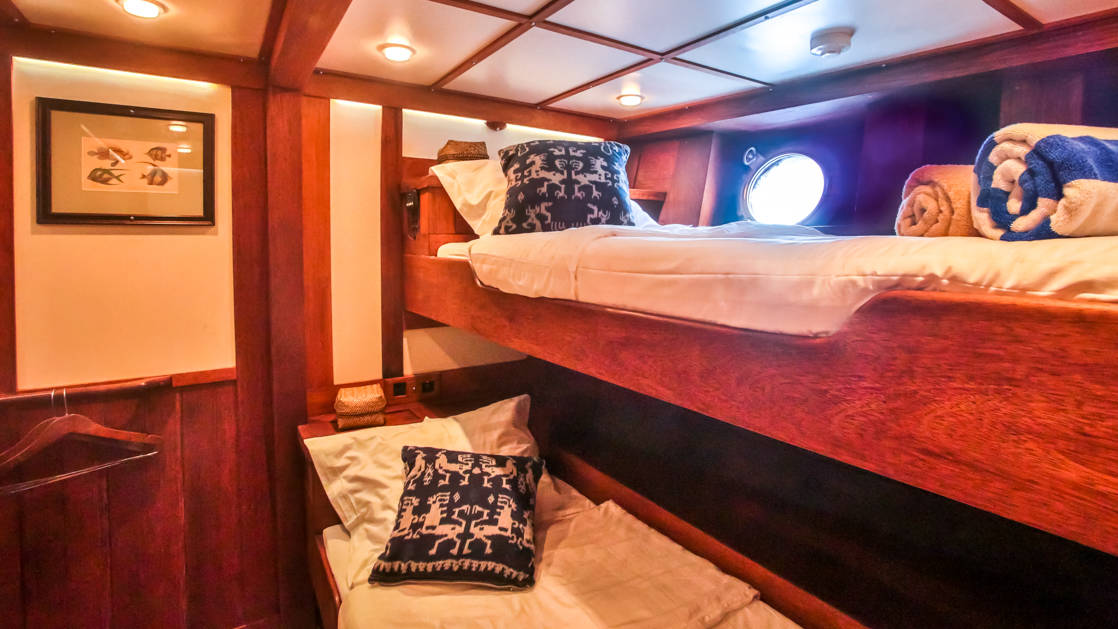 a cabin on the ombak putih small ship with stacked beds and a porthole
