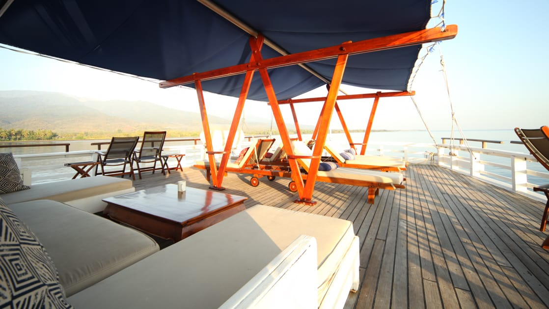 a sunny deck with large couches and a cloth shade aboard the ombak putih small ship
