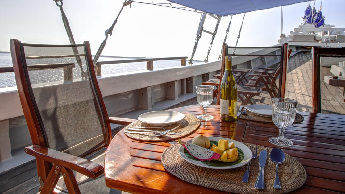 delicious food and a bottle of wine on a table on the deck of the ombak putih yacht on a sunny day